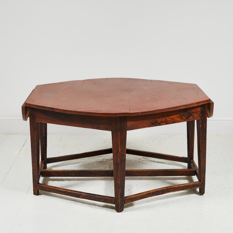 Rustic early 19th century French hexagonal table with two, drop leaves. Table offers two drawers, one of which is signed circa 1815. Cross base has beautiful aged markings.