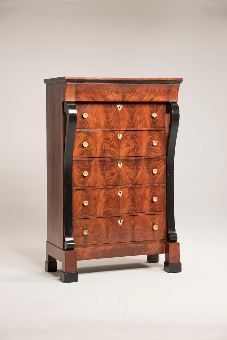 Early 19th century French mahogany chest of drawers. Five drawers plus an invisible one right below the top. The two curvilinear pilasters are lacquered in black color. This chest of drawers has been completely restored in a conservative way,
