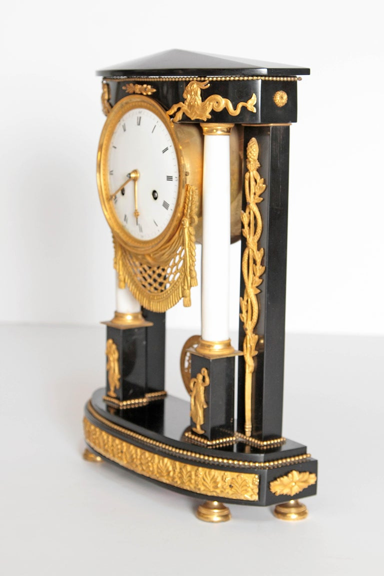 A French black marble neoclassic clock. Square columns at back with round white columns on pedestals framing round clock face. Delicate gilt bronze mounts embellish the whole. Serpentine twists at the sides, small ram figures at top of columns and