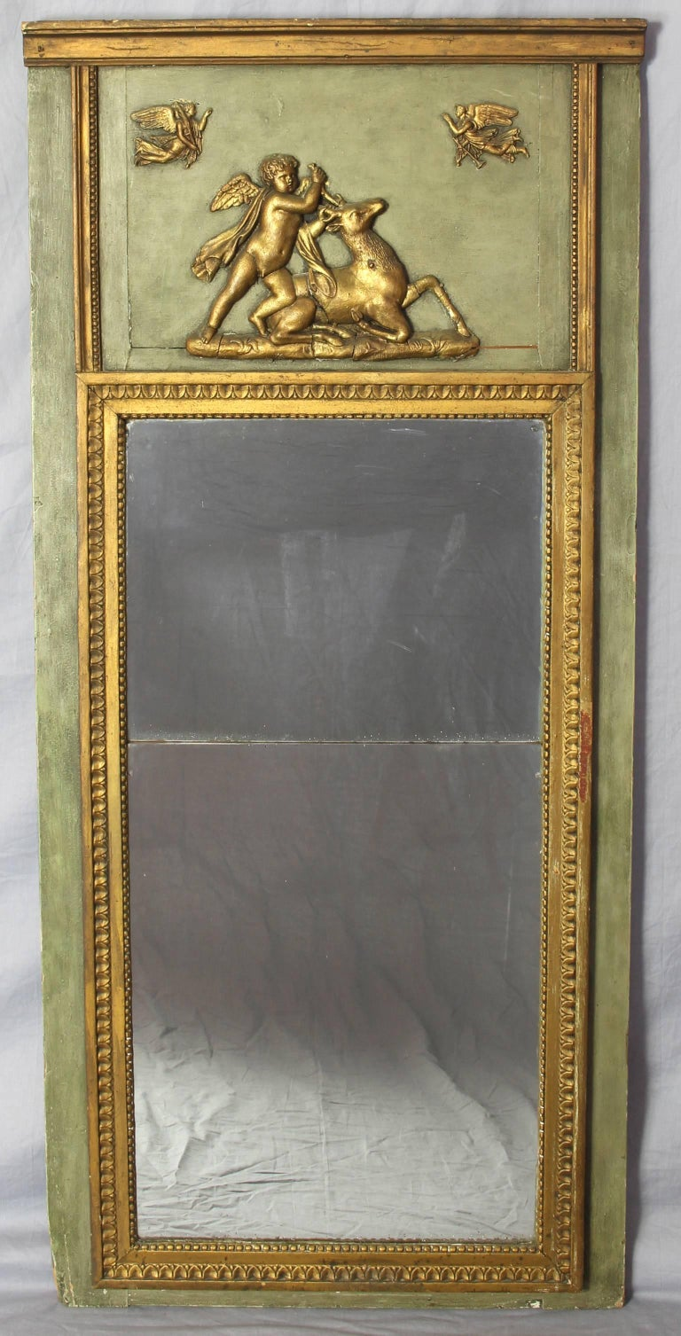 An early 19th C. French green paint and gilt decorated mirror with original glass, depicting classical motifs.