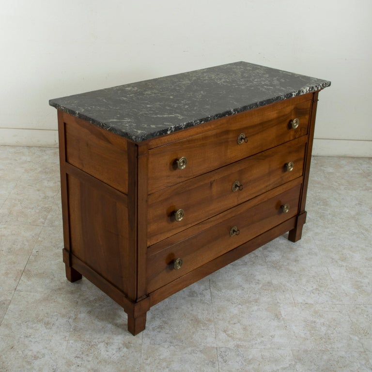 This French Restauration period walnut commode or chest of drawers from the early nineteenth century features its original Saint Anne marble top. Constructed of solid French walnut, its three drawers of dovetail construction are flanked by square
