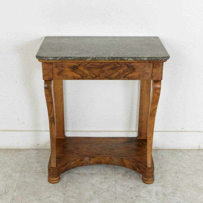 This small-scale early 19th century French Restauration period console table is constructed of stunning bookmatched walnut and is finished with a Saint Anne marble top. A single drawer of dovetail construction seamlessly forms the front of the upper