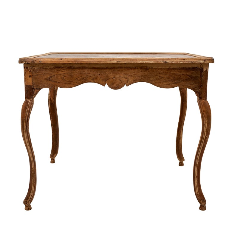 This Early 19th century French table includes an original tooled leather top and two drawers.