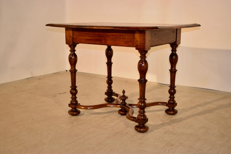 19th century French table made from walnut. The top is beautifully detailed with cross banding around the edges in a lovely pattern surrounding a central pattern with burl in a matching design. The top is finished with a beveled edge and follows
