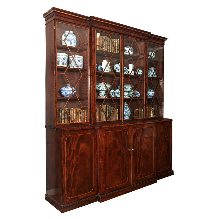 Early 19th century Georgian breakfront bookcase, Stamped Gillows of Lancaster. Its astragal glazed doors, line inlaid with satinwood, open to three shelves, with an oversailing molded cornice and over a satinwood and ebony-inlaid central cupboard,