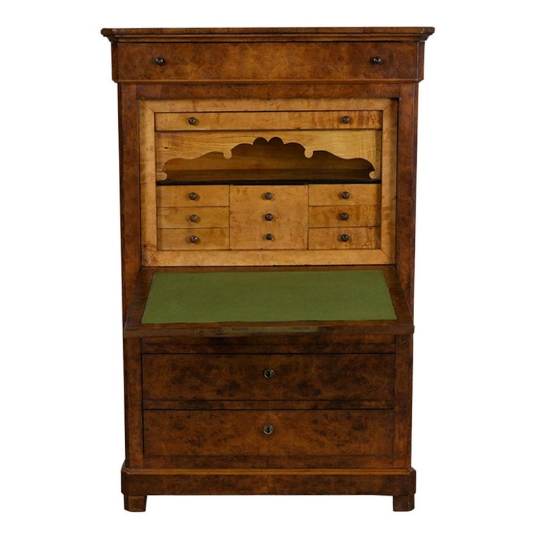 This Louis Philippe style Secretaire has been completely restored and has its original burled finish in very good condition. The piece features four large drawers, a drop-top desk with a green felt writing surface, in the interior 6 small drawers, a
