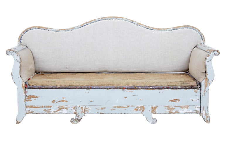 Early 19th century Gustavian painted pine sofa bed, circa 1820.  Good quality piece of rustic Swedish furniture. Large in scale with a deep shaped back. Scroll carved arms. Removable seat allows the bottom section to be pulled out and be used as a