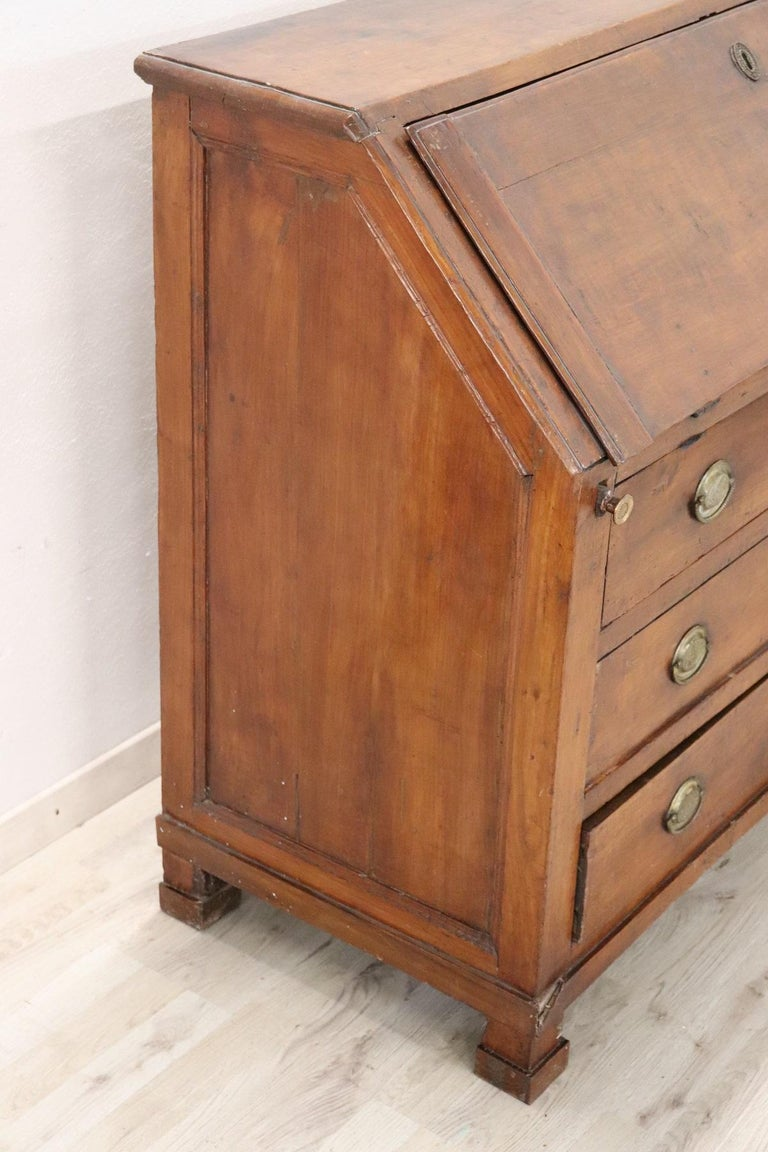 Important antique Italian Empire chest of drawers 1805s in solid walnut wood. Simple line essential wood of beautiful antique patina. Three large and comfortable drawers. At the top, the door opens and becomes a comfortable writing surface with