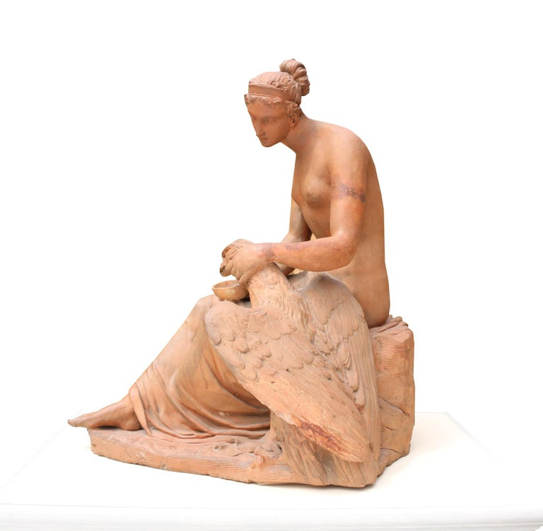 An early 19th century Italian terracotta group of Hebe and the eagle, she sits offering the eagle refreshment from a shallow bowl. Shown on a modern timber plinth.