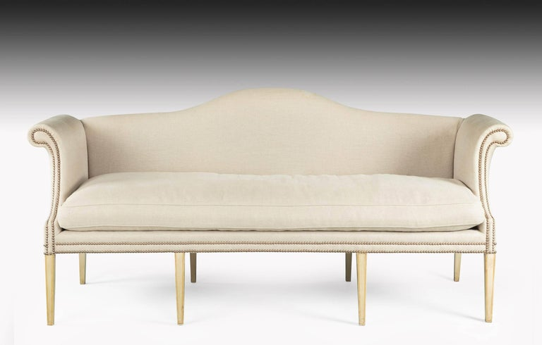 A large camelback sofa, the framework of ivory paint original, but now somewhat tired. 