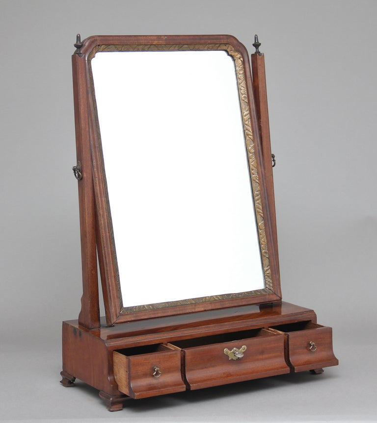 Early 19th century mahogany dressing table / toilet mirror, with a swivel mirror, the frame decorated with wooden finials on top, the base section having three oak lined drawers, standing on small ogee feet, circa 1800.