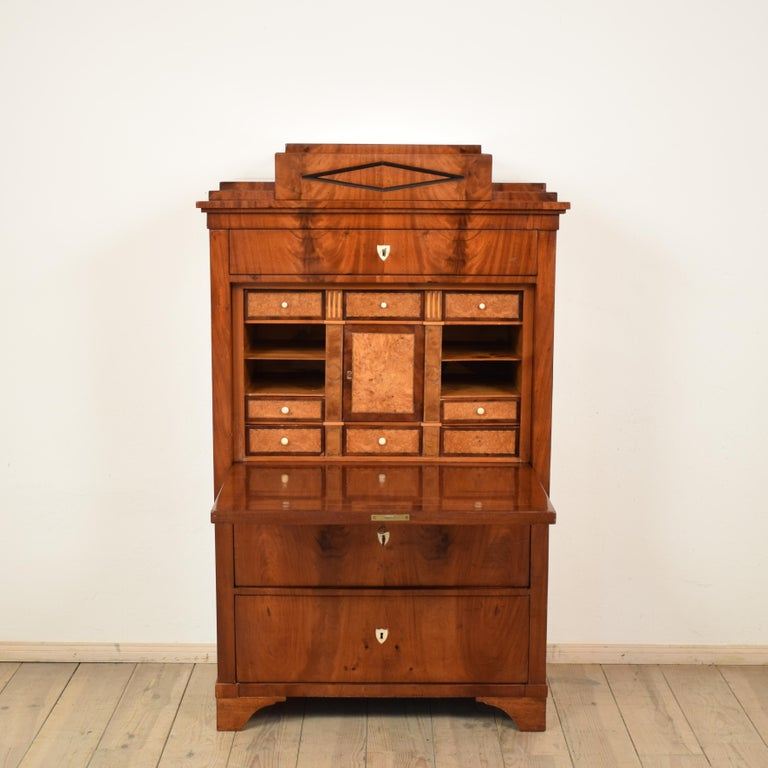 This Empire secretary was made in Germany, circa 1810. It is mahogany veneer on oak. The inside its veneered in birch. The architectural design is typical for this period. A very fine furniture which fits into a modern or classical home.