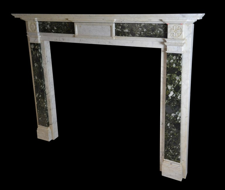 An early 19th century mantelpiece of architectural form in Carrara marble with end blocks carved with simple rosettes above inverted tapering pilasters in brecciated verde marble and conforming frieze panels, the latter flanking a plain fielded