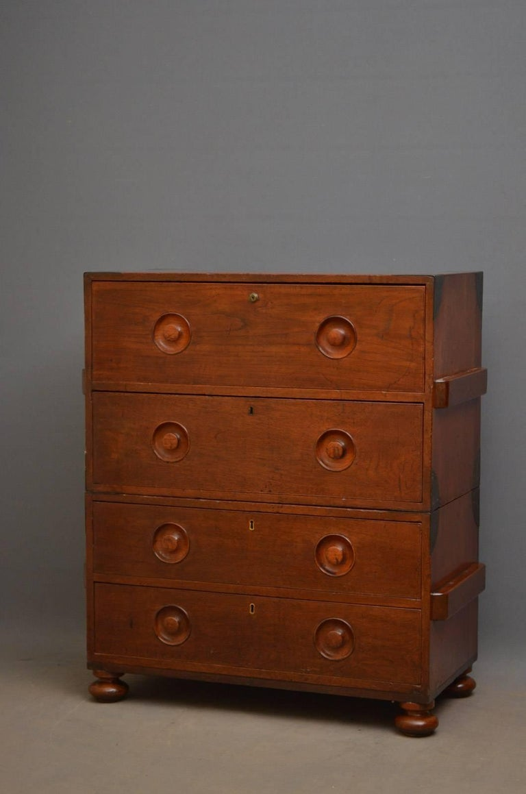 Sn4304 early 19th century teak secretaire Campaign chest of drawers, having metal bounds and four graduated drawers, one being a secretaire, all fitted with original turned and recessed handles and carrying handles to sides, standing on turned feet.