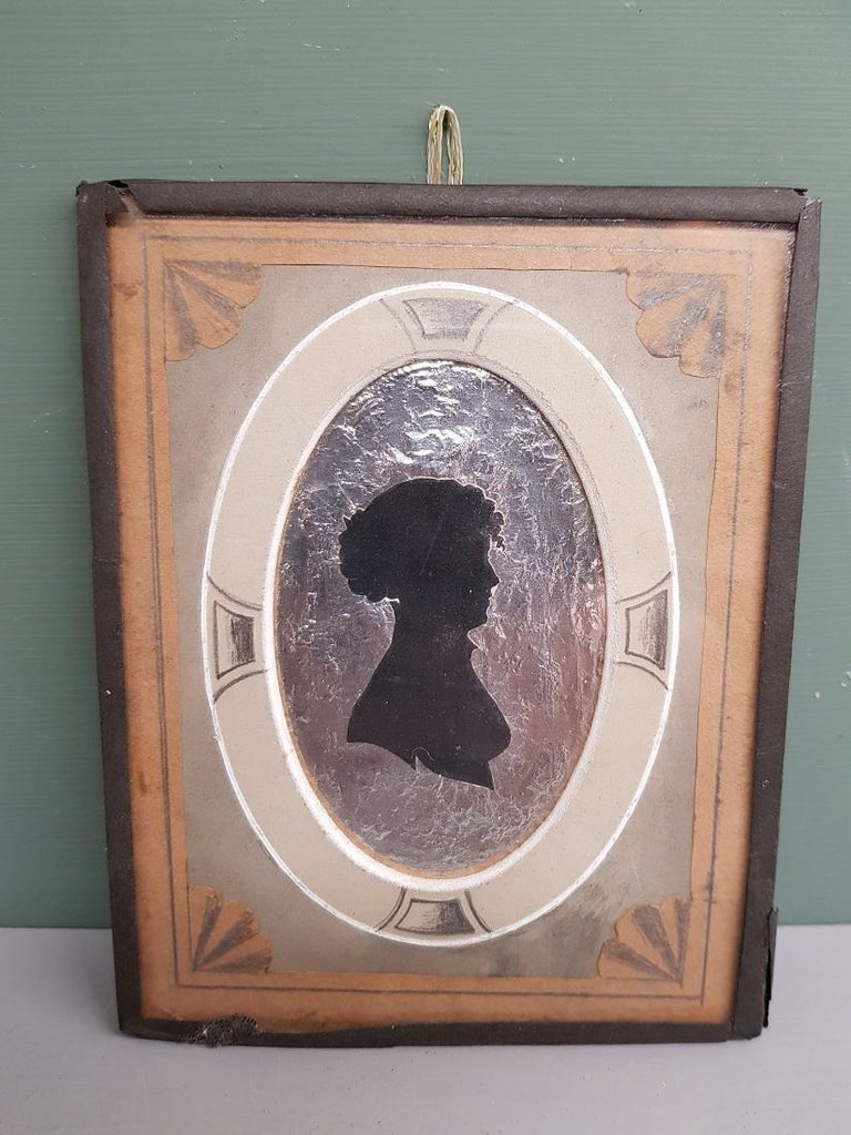 Antique miniature silhouette with image of a lady on a silver / aluminum-like background and a passe-partout colored in pencil, on the back is the description of the lady, which is furthermore in a good condition for his age. Originating from the