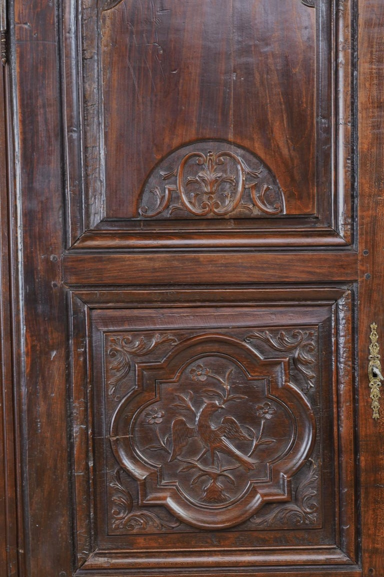 A lovely bonnetiere in walnut with carved embellishments on the door panels that include fleur-de-lis and birds that may be starlings, France, circa 1820. Measured from the crown molding:  33