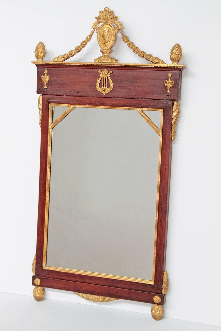A mahogany and giltwood neoclassic mirror. Portrait of Classic figure in oval at top with swags to frame. Applied urns as sides and lyre in center, all gilt as well as around mirror. Additional decorations on sides and as the corners. Early 19th
