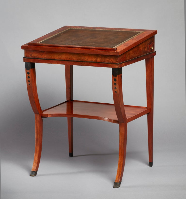 A rare early 19th century neoclassical mahogany double ratcheted reading-cum-drawing-table. The slightly sloped top with an inset tooled leather writing surface. The double ratcheted top turns this elegant reading table into a standing desk. With