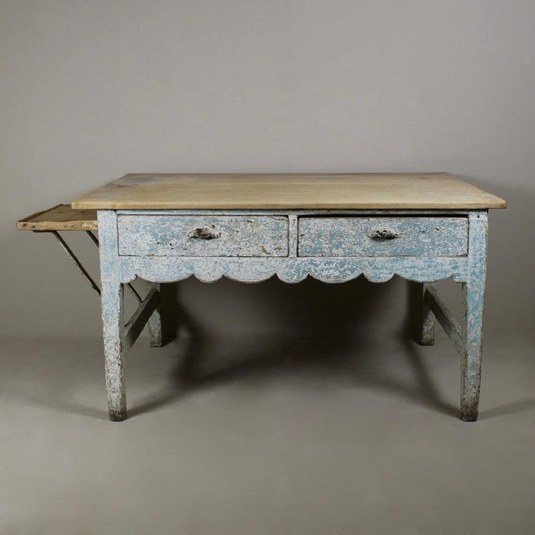 A truly wonderful, English, early 19th century, original painted pine bakers table. With its original beautiful, pale scrubbed sycamore top, wavy line side rail, two drawers and unusual bracketed side shelf. The painted base retaining many layers of