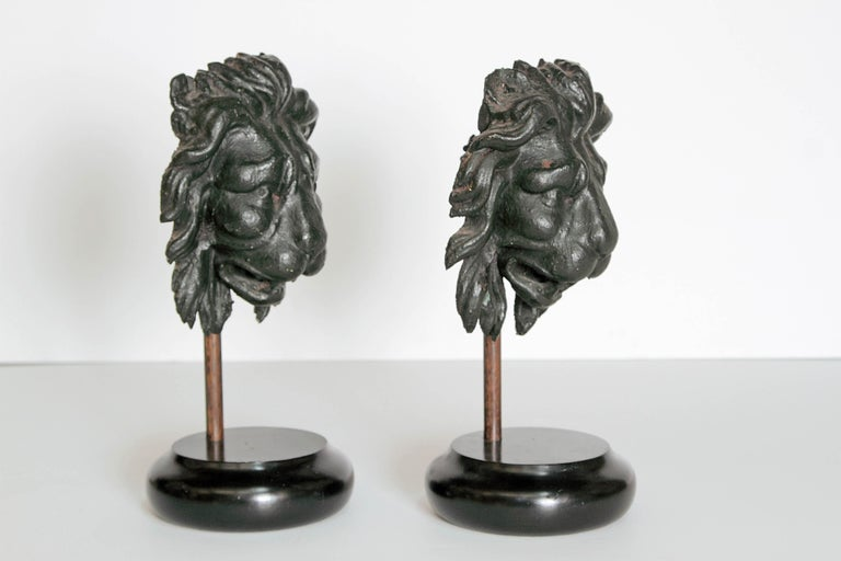 A pair of heavily carved wood lions heads, realistically carved and mounted on carved round wood bases.