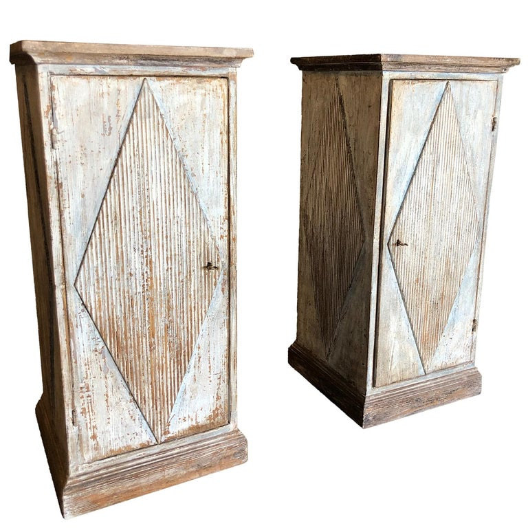 A rare pair of Gustavian square pedestals with raised rhombic decoration on front and sides with chalk painted finish on wood. The front panel opens, key included. Wear consistent with age and use, circa 1820, Scandinavia.