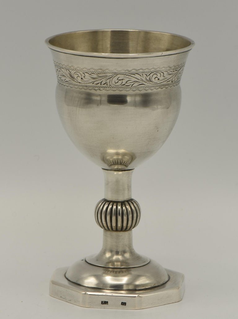 Handmade silver Kiddush goblet, Poland, circa 1820.  Large upper portion engraved with floral decoration, set on a bulbous scroll stem on a octagonal base. Clearly struck with the quality mark 12 and maker A.G.  Kiddush cup is a ceremonial vessel to