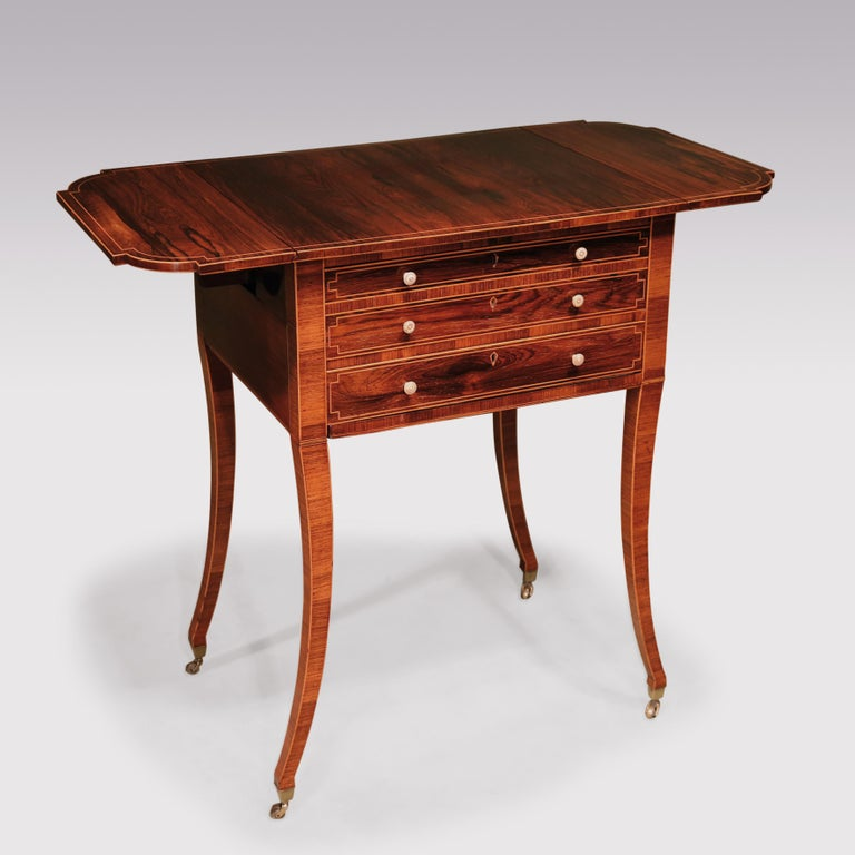 A fine quality early 19th century Regency period rosewood occasional table boxwood strung throughout, having rectangular top with breakfront bowfront flaps above 2 frieze drawers and workbox, supported on unusual cross-grain veneered sabre legs