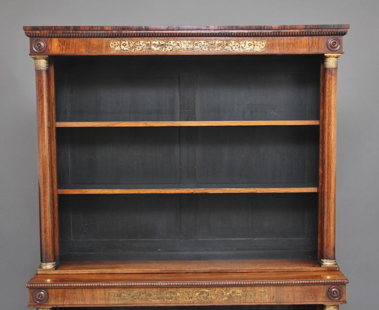 Early 19th century rosewood and brass inlaid open bookcase, the moulded edge top having carved beading running along the front and sides, wonderful brass inlaid pattern on the top and bottom frieze, turned columns decorated with brass capitals,