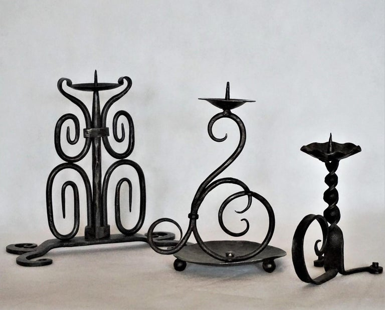 Set of three heavy, hand forged iron church candleholders, Spain, early 19th century.
