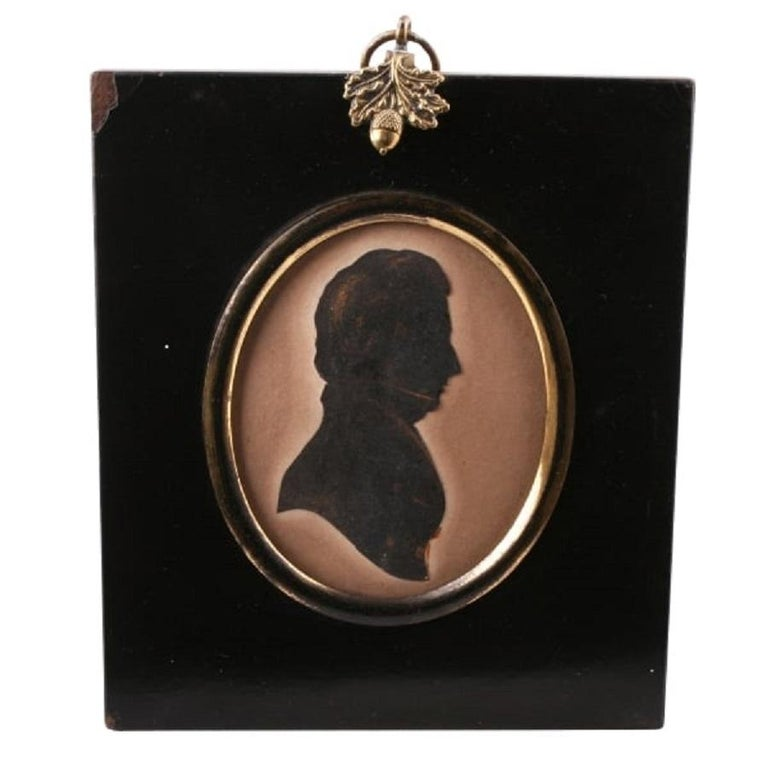 An early 19th century Regency period silhouette of a Gentleman.  The silhouette is fitted in a gilded brass oval frame with a domed glass cover and is held in a black lacquered oblong frame.  The frame hangs from a gilded brass ring that has an