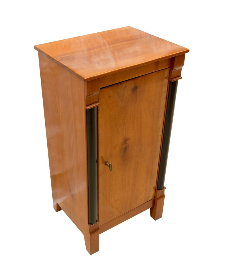 Original Biedermeier solid cherrywood nightstand or pillar cabinet from Germany. Back and shelf is made of pinewood as usual. The opening handle is made of brass. The furniture is in a very good, restored condition.