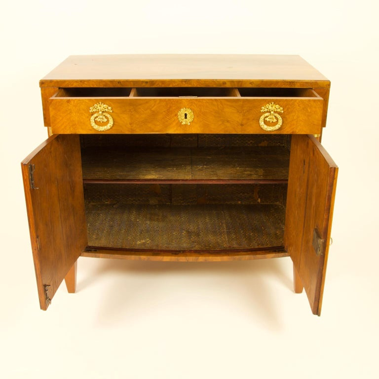 Early 19th century South German or Austrian Biedermeier walnut cabinet dresser  The rectangular body standing on four small tapering feet holding a cabinet section opening with two slightly concave doors to the inside with one shelf. The doors are