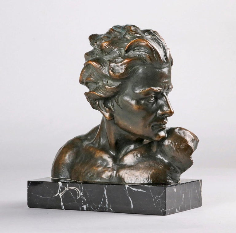 Beautifully expressive statue from the Art Deco period, bust of a young man. The statue is made of terracotta with a black marble base. The statue is patinated in a green bronze color. On the back is the signature of the artist, Johannes Dommisse,