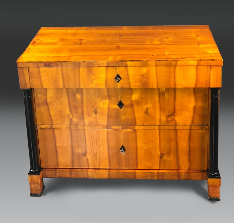 Early 19th century Biedermeier commode with beautifully matched cherrywood veneers of Swedish origin. One small drawer above 2 large ones flanked by black lacquered Doric style columns. All drawers have rhomboid shaped buffalo Horn keyhole
