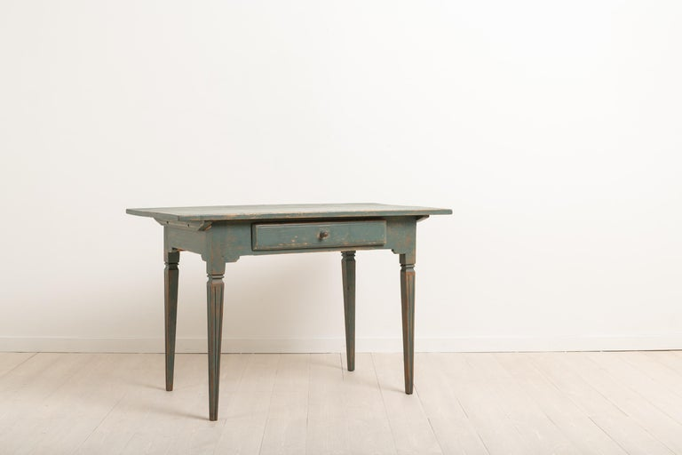 Gustavian side table with straight tapered legs. The legs are decorated with flutes. Distressed dark green paint. The table has a single drawer which has its original wooden knob. Manufactured around 1810-1820 in northern Sweden. The side table is