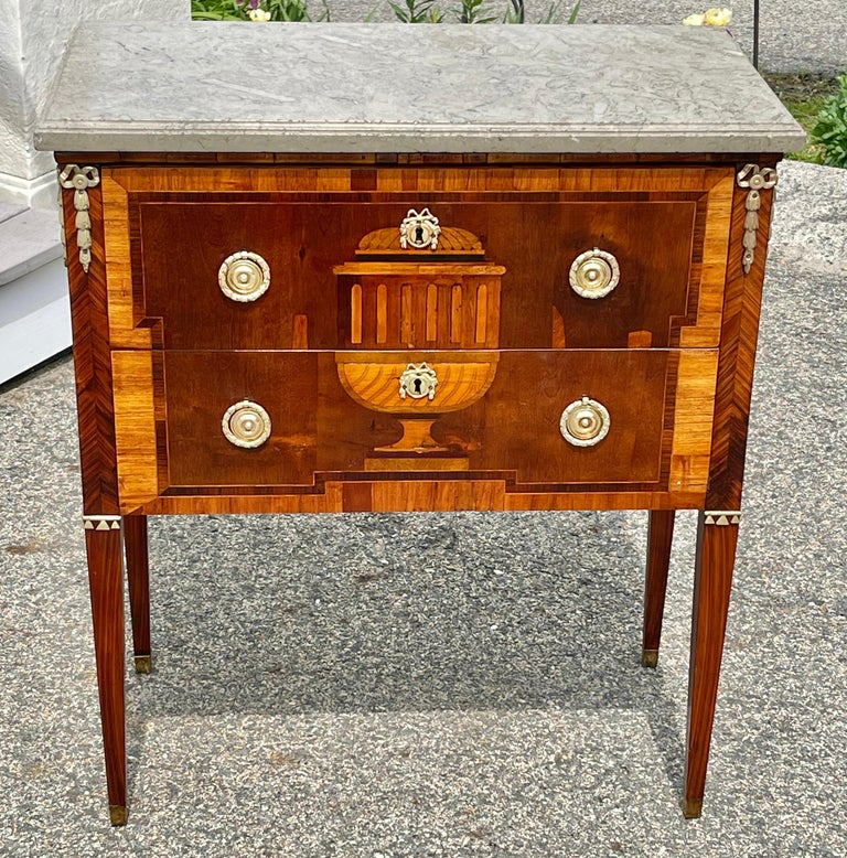 Early 19th century Swedish satinwood and fruitwood commode. Neoclassical period with original fossilized marble top. Original locks etc. Rare urn front motif with equally rare bowed laurel wreath inlays.  Exquisite.