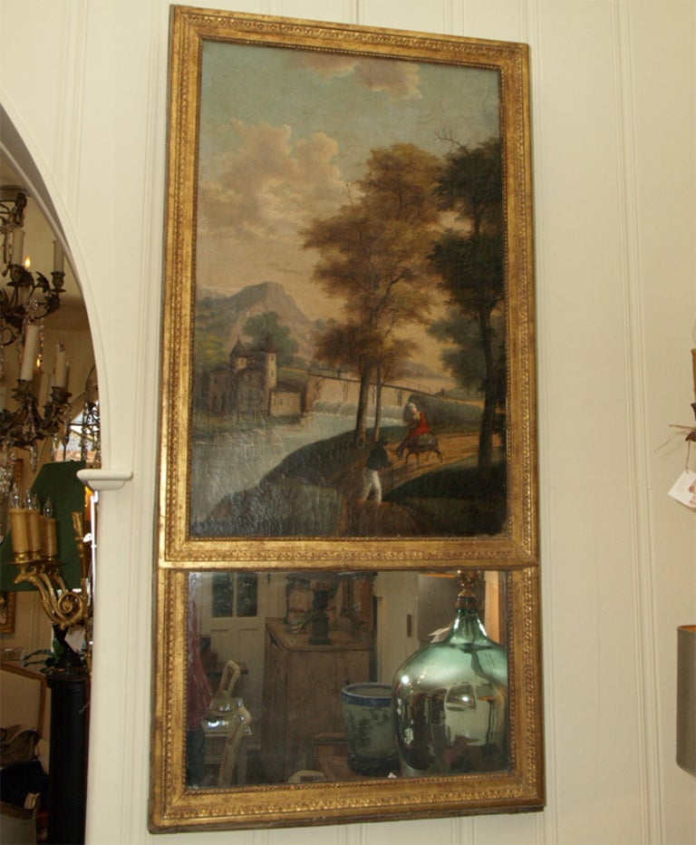 A finely painted naïve landscape with castle, a stone bridge over a small river with 2 figures in the foreground, a woman riding a donkey and a man walking on the road. Original mercury mirror, decorative frame with original gilt.