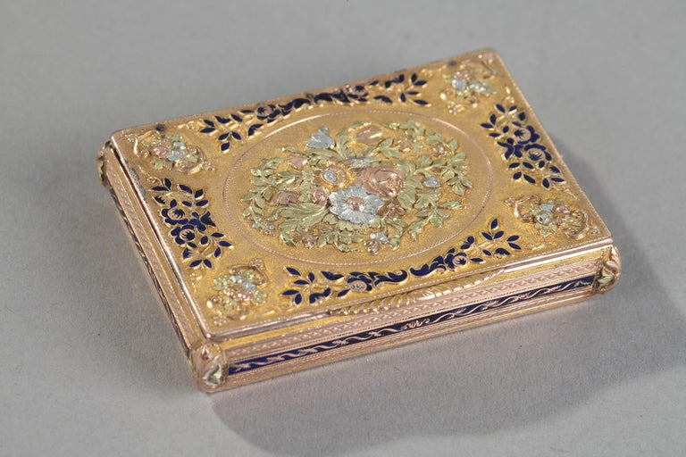 Rectangular box with three tones of gold and royal blue enamel. The hinged lid is embellished with a multicolored gold medallion in relief featuring a bouquet of roses and tulips, set on a matte gold background. Delicate foliage accented with royal