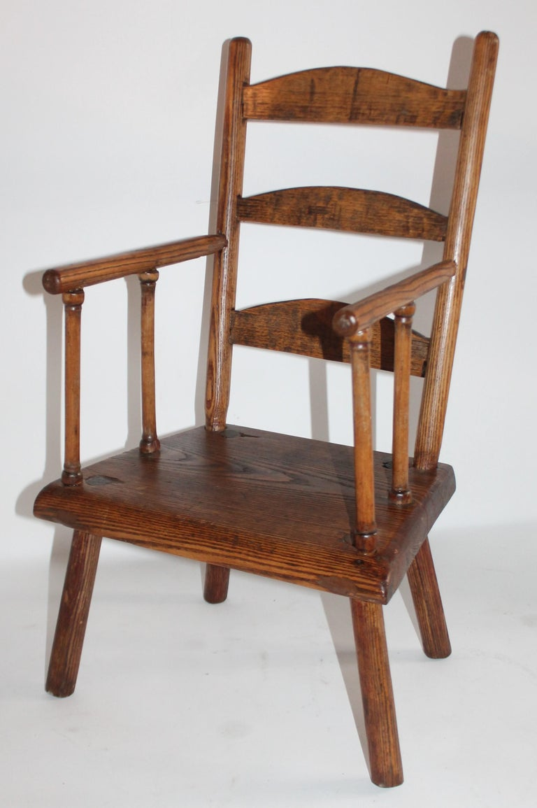 Early 19th century ladder back child's chair from New England in fantastic condition. This early chair is mortised and square nail construction.