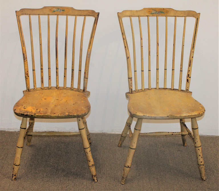 These fine early original yellow painted New England Windsor chairs are in good condition. They are paint decorated floral pattern on the front of the inside slat. They have minor paint loss throughout as seen in the pics with a nice patina surface