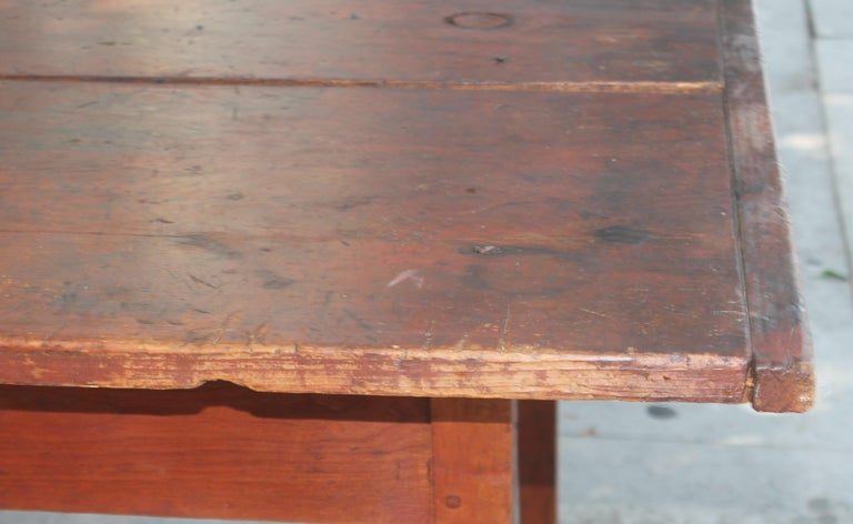 Early 19thc original red painted farm table from Pennsylvania in very good sturdy condition. The taper legs are amazing and two board top. There are four early hand made screws from the early 1800's in the top of the table. Probably put in years