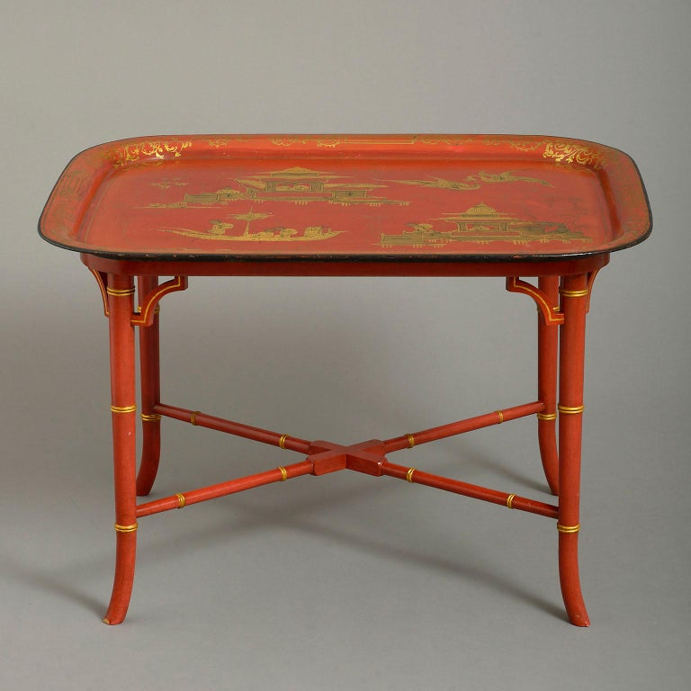 An early 19th century Regency japanned tole tray forming a coffee table, decorated with chinoiserie scenes on a sealing-wax red ground and with later conforming vogue Regency stand.