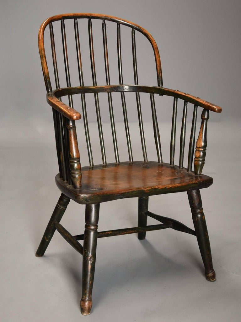 A superb early 19th century West Country ash and elm hoop back Windsor chair with wonderful patina (color) and original green paint finish.  This chair consists of a hoop back with hand drawn spindles leading down to the arm bow with further