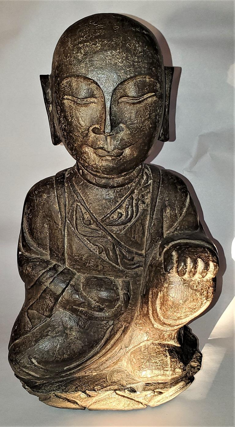 Presenting a lovely early 20th century Japanese stone carved Buddha.  Made of green/brown solid stone… this statue features a kneeling Buddha with one hand on his bended knee and the other holding an offering.  Probably made in the first quarter