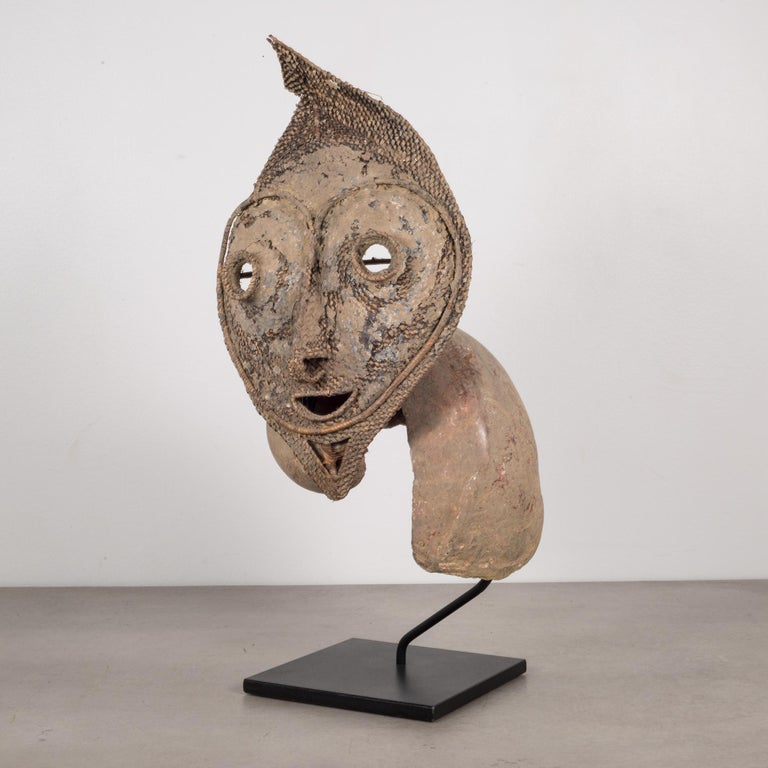 About  An Oceania, Papua, New Guinea, East Sepik, Boiken People Talipun mask mounted on a custom steel stand. A 'talipun' consists of a large piece of the sea snail attached to a woven ancestral face.   Creator: Boiken People, Papua New