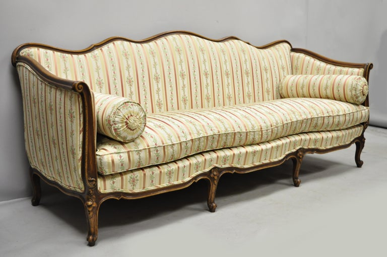Early 20th century French Louis XV Provincial style sofa with serpentine carved back originally sold by W & J Sloane. Made in Italy. Item features serpentine carved rails, pink striped silk upholstery, solid wood frame, beautiful wood grain,