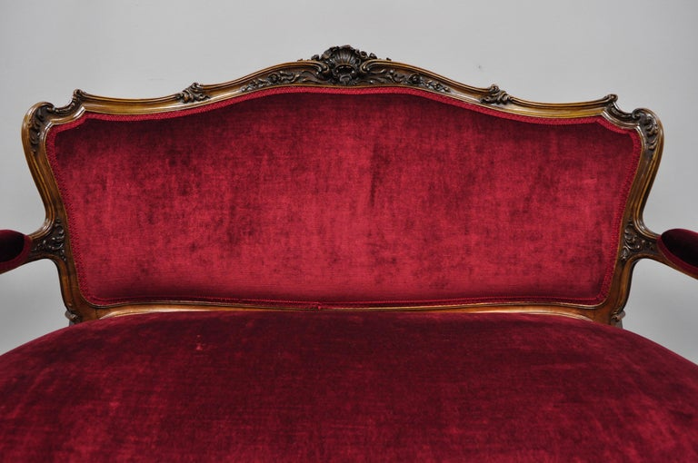 Early 20th century French Louis XV style shell carved mahogany sofa settee in red fabric. Item features shell carved top rail, solid wood construction, beautiful wood grain, upholstered armrests, cabriole legs, very nice antique item, circa early