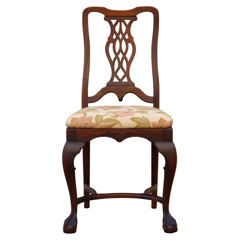 George II-style carved walnut side chair with trapezoid drop in seat, cabriole legs, curved H stretcher and claw and ball feet by Brower Furniture, Grand Rapids MI, circa 1920s. The seat is upholstered in new fabric with coral and green florals