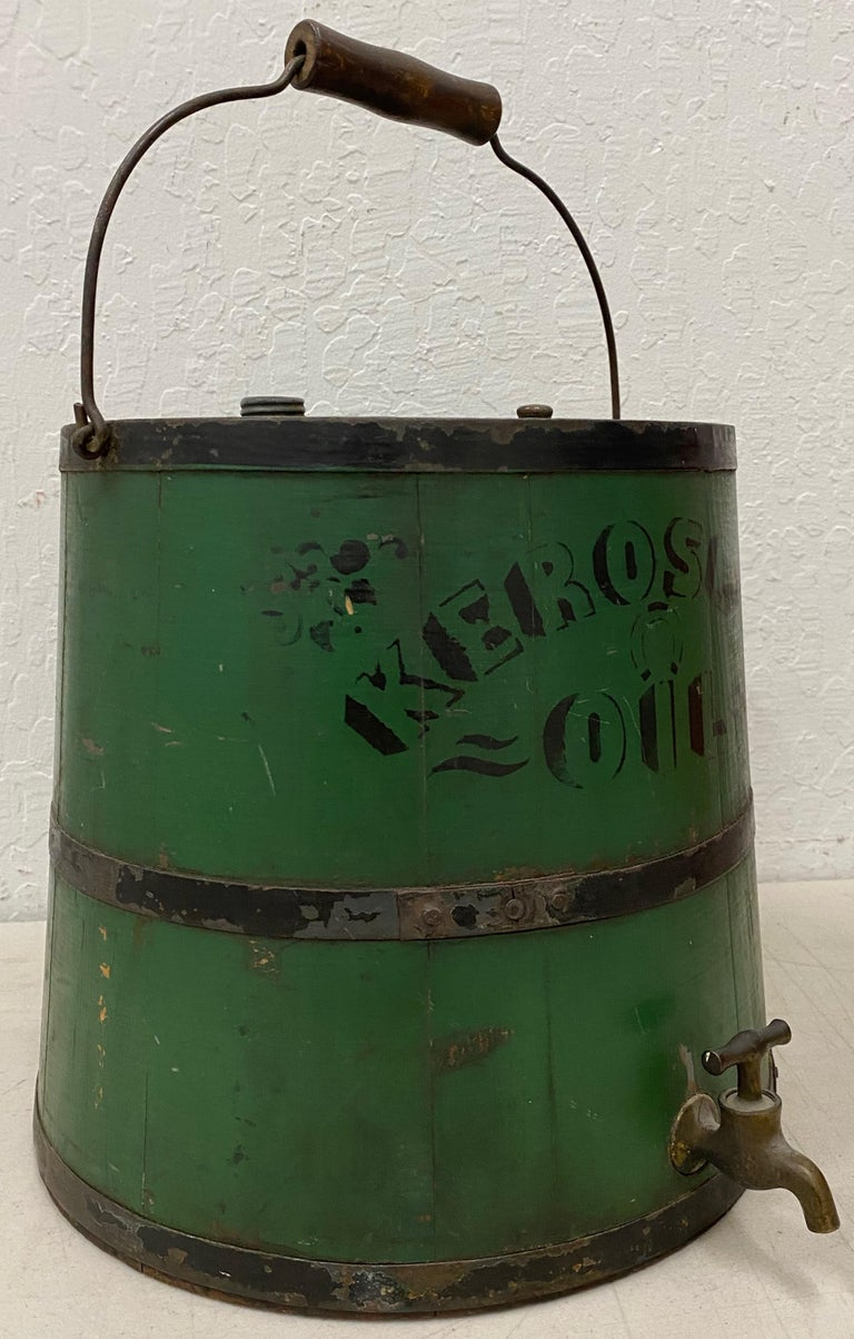 Early 20th century green kerosene can  Fantastic old school wooden and metal strap handmade kerosene oil can.  Though we don't use the cans today, kerosene lamps were in most every household in America in the 19th and early 20th