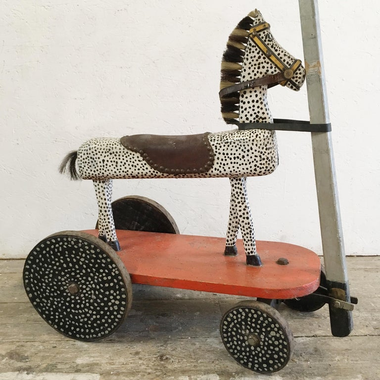Handcrafted French childs pull along wooden horse. Fantastic hand painted spotty wooden horse on wheeled base, pull along handle. The wheels have also been painted spotty in black and white, opposite to the horse, circa 1930s-1950s. The horse